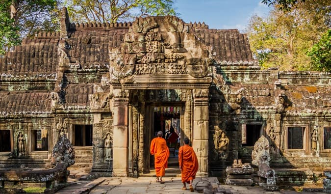 Two monks in orange robes walking in a temple in Cambodia