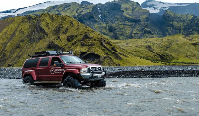 A jeep from Midgard Adventures crossing a wild river in Iceland
