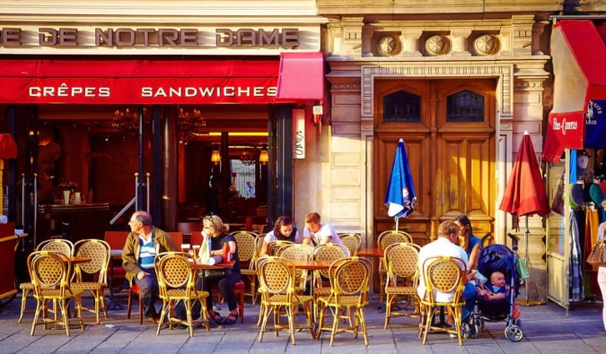 Locals and travelers sitting at a cafe in Paris, France