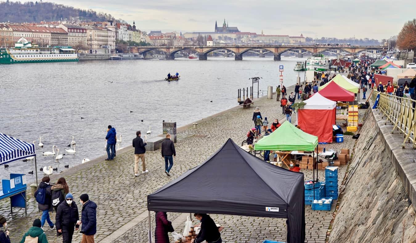 People walking near stalls along the river in Prague, Czechia