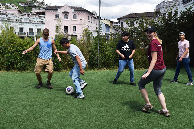 students playing soccer with local children in Ecuador
